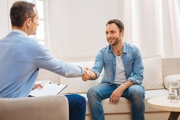 smiling man shaking hands with counsellor